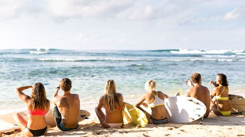 group of men and women sitting on beautful beach with surfboards