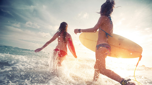 Picture of two girls going for a morning surf