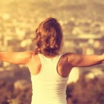 girl standing on a mountain with her arms out horizontal