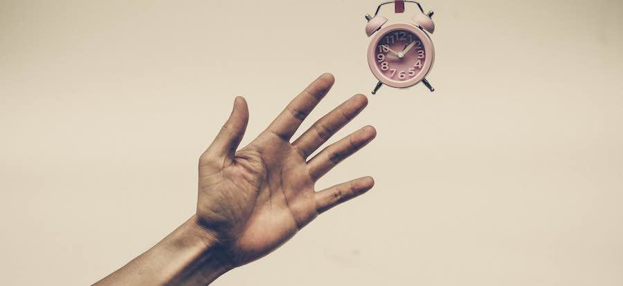 hand reaching for an alarm clock