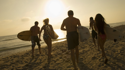 Five people running in for an early morning surf