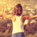 woman standing with arms wide open feeling energised